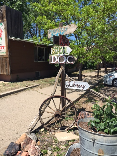 An old-fashioned sign in Broadus points the way to the saloon and other local institutions.