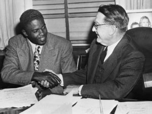 Jackie Robinson shakes Branch Rickey's hand after signing his 1948 contract. February 12, 1948 New York City, New York, USA