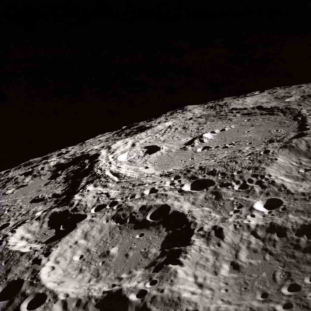 A moon viewed from above, full of craters