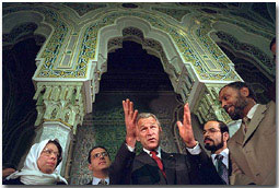 """After addressing the media, President George Bush talks with his hosts during his visit to the Islamic Center of Washington, D.C. Sept. 17, 2001. """"And it is my honor to be meeting with leaders who feel just the same way I do. They're outraged, they're sad,"""" said the President during his remarks. """"They love America just as much as I do."""". White House photo by Eric Draper."""