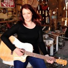Georgia posing holding guitar inside a barn