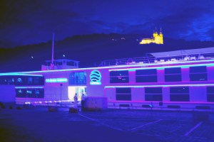 Our ship aglow at night with Fortress in background
