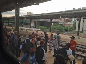 Smokers and passengers mix on the Birmingham station platform.