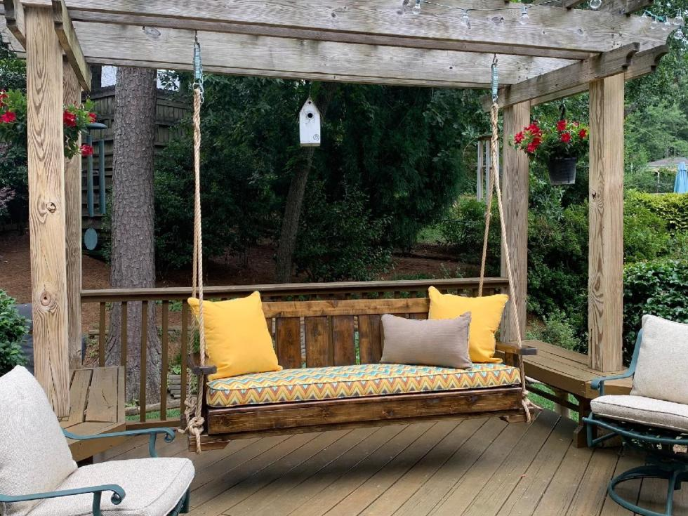 Porch swing with cushion, pillows, and rope