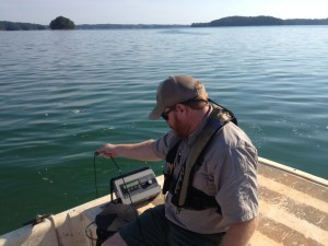 Fisheries Technician Chris Looney drops a dissolved oxygen probe in Lake Lanier to measure a reservoir profile near Buford Dam.