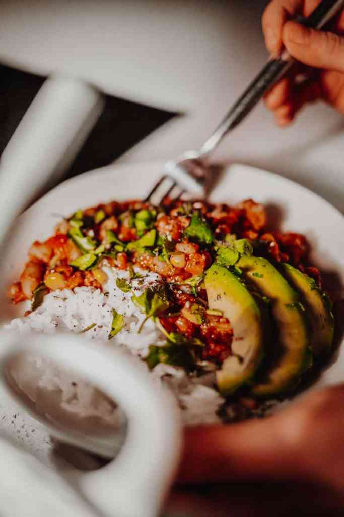 A bowl of Mixed-Bean Veggie Chilli with rice and avocado.