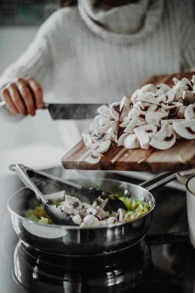 adding the mushrooms into the saucepan