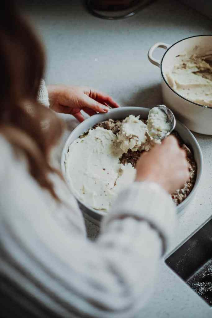 topping the leek & mushroom pie with mash potato
