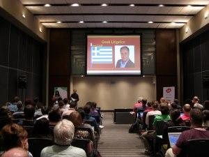 """Διάλεξη σε κοινό, στο κέντρο υπάρχει slide με τίτλο """"Greek Litigation"""", την Ελληνική σημαία, και φωτογραφία του Θεόδωρου Κατσανέβα."""