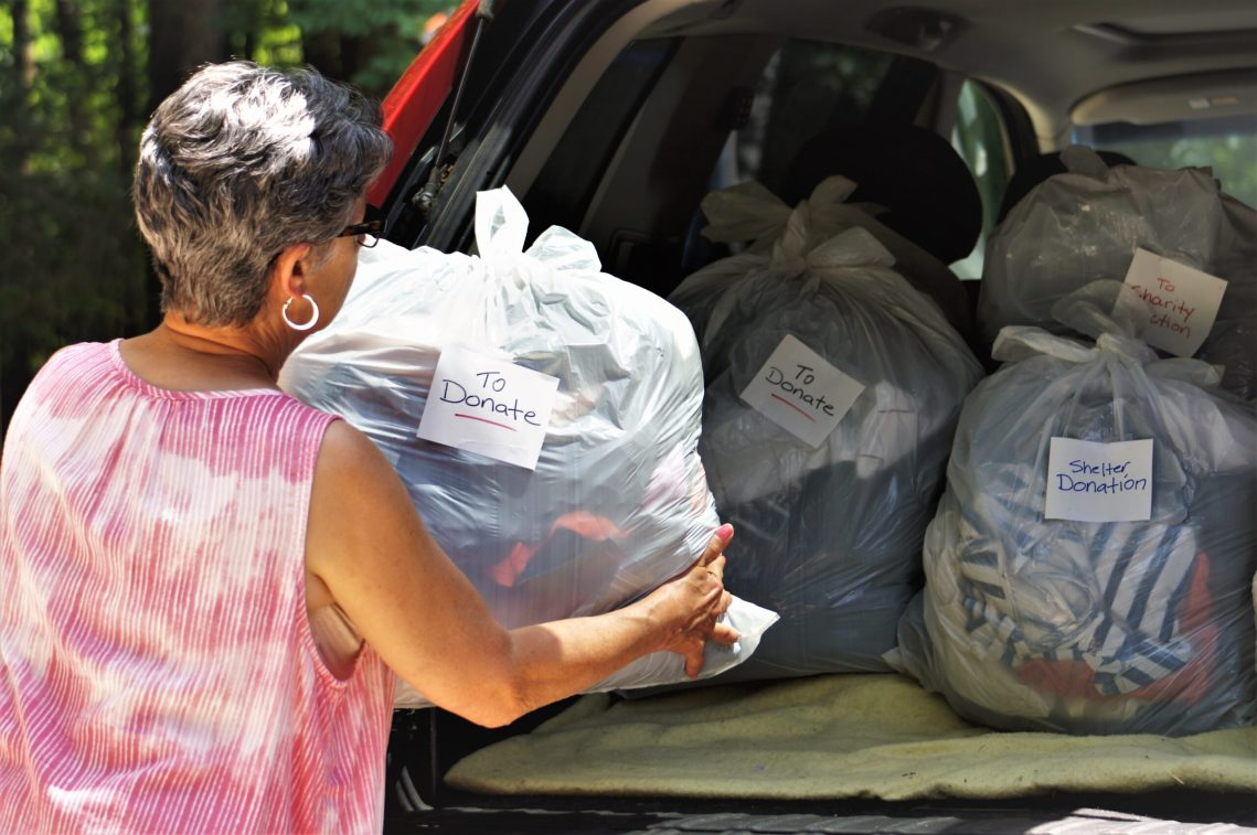 woman loading car with bags for charity