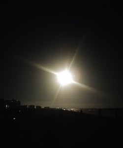 The bright light of a rocket engine taking off in the night