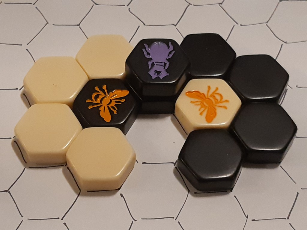 Two queens are each surrounded by tiles, with only one empty cell between them. A beetle is positioned to climb into the hole, which would completely surround them both.