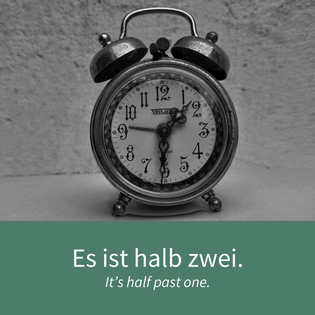 "Image showing am a clock and the caption ""Es ist halb zwei. - It's half past one."""