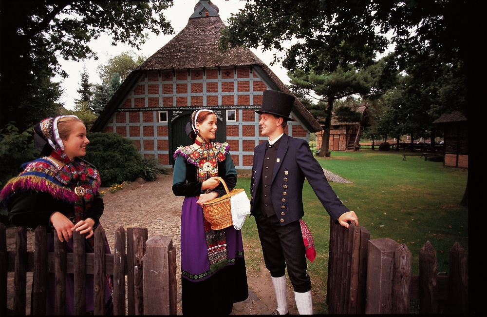 Beeksheepers in costume by half timbered farmhouse