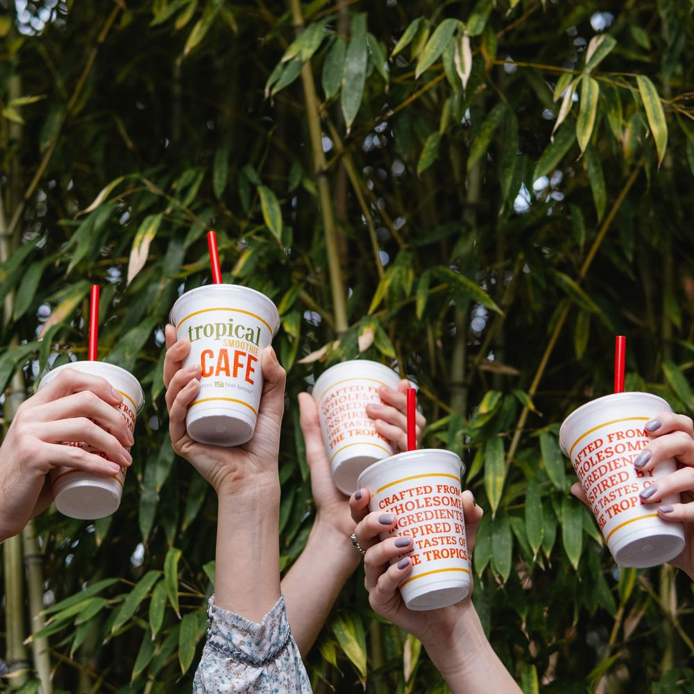 People Cheers with Tropical Smoothie Cafe Drinks