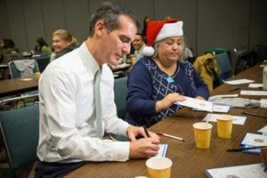 Photographed is the mayor of Los Angeles Eric Garcetti on left and USC Gerontology alumna Laura Trejo on right write cards to accompany holiday gifts for seniors as part of Project CARE.