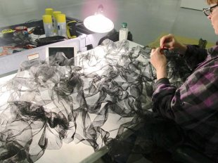 close up detail of Artist Gerri Sayler working on black mesh for Terra Ignis art installation at Nicolaysen Art Museum