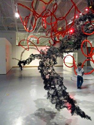 viewer walking through Terra Ignis art installation by Gerri Sayler at Nicolaysen Art Museum