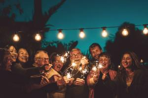 Happy family celebrating with sparkler at night party outdoor
