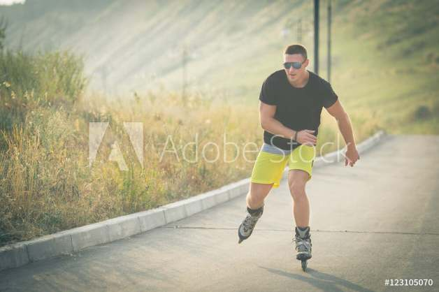 young man with inline skates ride in summer park outdoor rollerskater