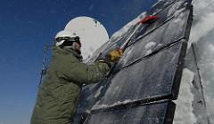 Cleaning solar panel on Kodiak Island (U.S. Coast Guard photo by Petty Officer 1st Class Sara Francis)