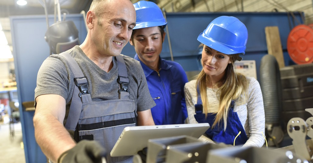 three factory workers looking at tablet on factory floor freepoint technologies