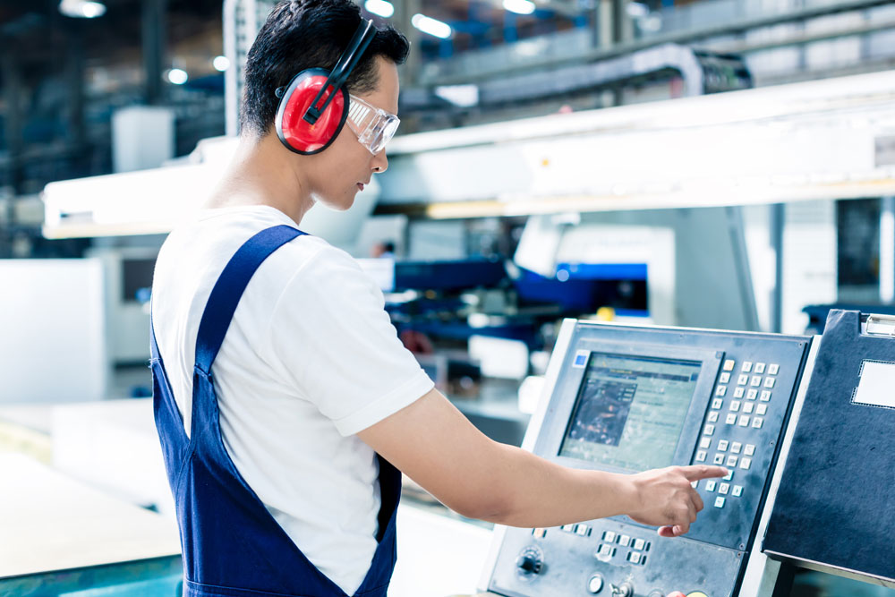 factory worker entering data in CNC machine at factory floor wearing safety glasses and ear protection measure analyze share freepoint technologies