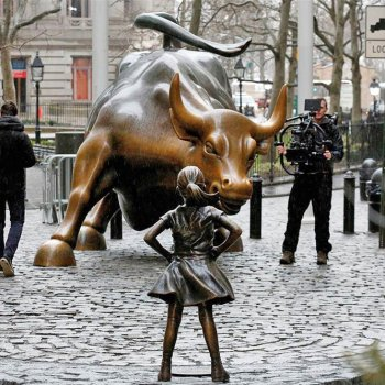 Photo of the statue of girl placed in front of bull on wall street