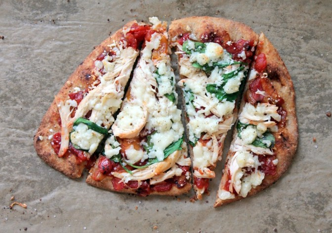 Oval shaped pizza topped with spinach, pulled chicken, tomato-mango chutney and melted queso fresco