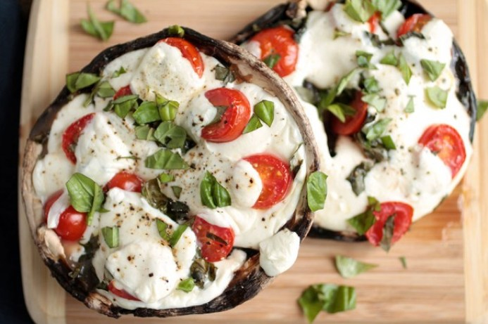 Two large portobello mushroom pizza crusts topped with mozzarella, grape tomatoes and basil