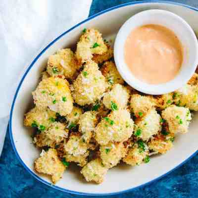 Whip up this healthy and delicious crispy cauliflower bites appetizer with sriracha dipping sauce for your next party.