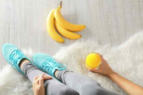 Woman sitting on floor with banana and juice