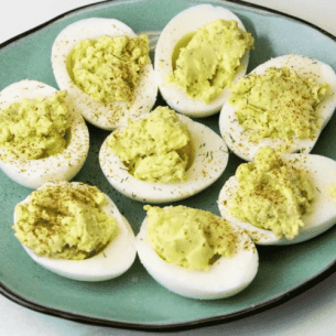 Avocado deviled eggs sitting on blue plate sprinkled with dill and paprika