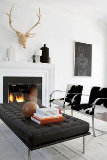 The wooden antlers exceeding the fireplace emphasis this contemporary living room.