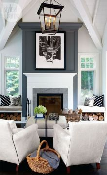 This snowy living room beams with natural light shining on either side of the fireplace.