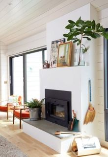 A tropical fireplace adorned with a lengthy branch and large portraits.