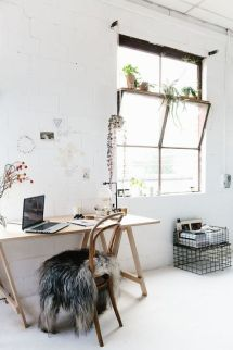 A timber desk and chair set with a large open window on the side.