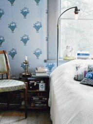 Blue wallpaper adds a pop of color to this neutral bed set.