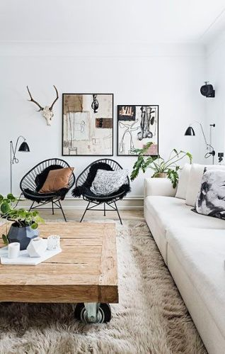 A wooden coffee table on wheels topped with a plant makes this space cool and rustic.