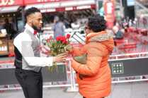 Former pro-football player Rashad Jennings surprising a New Yorker with a red rose from 1-800- Flowers.com in Times Square on Valentine's Day