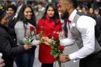 NYC visitors stop and receive a 1-800-Flowers.com red rose from former pro-football player Rashad Jennings in Times Square on Valentine's Day