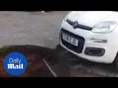 Moment womans car is pulled out of 20ft deep sinkhole in Swansea - Daily Mail