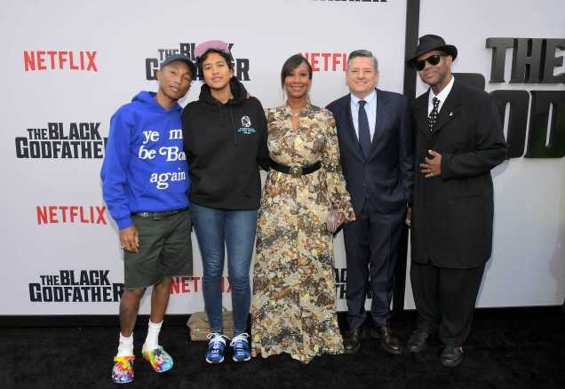 "LOS ANGELES, CALIFORNIA - JUNE 03: Pharrell Williams, Helen Lasichanh, Nicole Avant, Netflix Chief Content Officer Ted Sarandos and Jimmy Jam attend Netflix world premiere of ""THE BLACK GODFATHER at the Paramount Theater on June 03, 2019 in Los Angeles, California. (Photo by Charley Gallay/Getty Images for Netflix)"