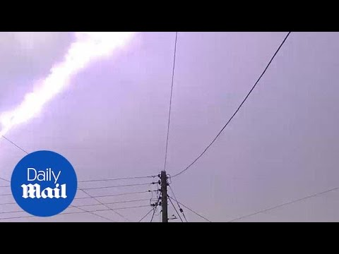 Incredible 'one in a million' moment bolt of lightning strikes rainbow's curve
