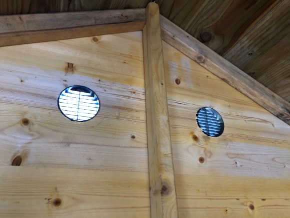 Two circular vents installed in a shed, viewed from the inside of the shed.