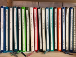 Notebooks lined up on a bookshelf dating back six years.