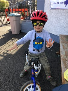 Sam on his bike holding up his hands.