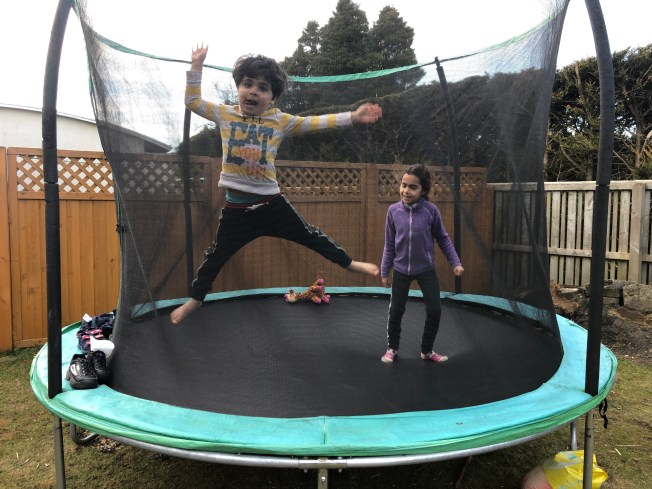 Kids jumping on a trampoline.