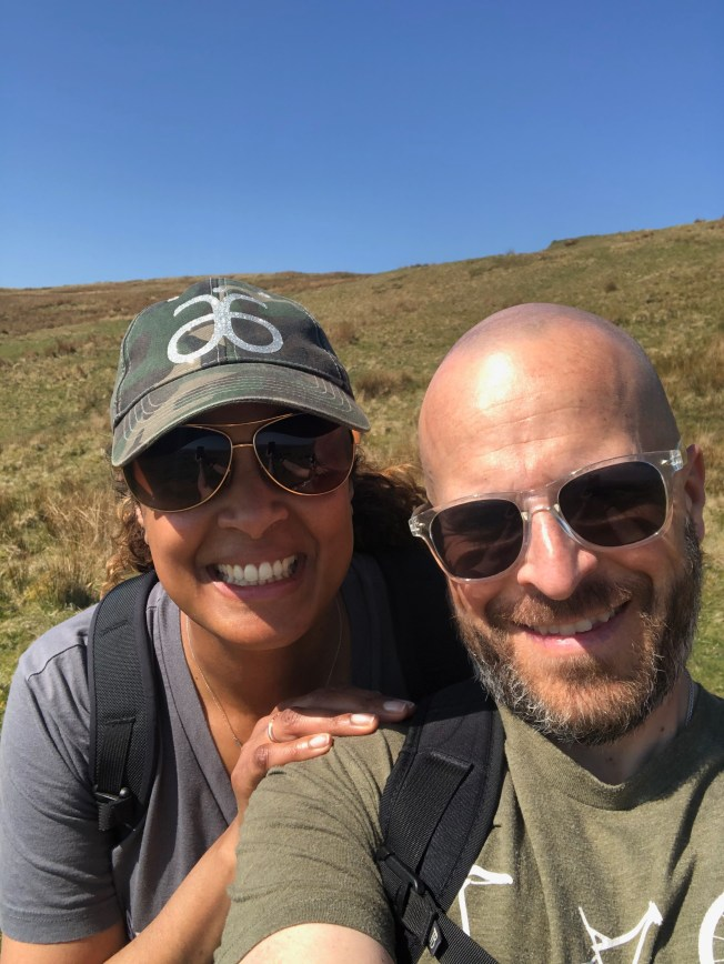 Selfie of my wife and I on a hike with sunglasses on.