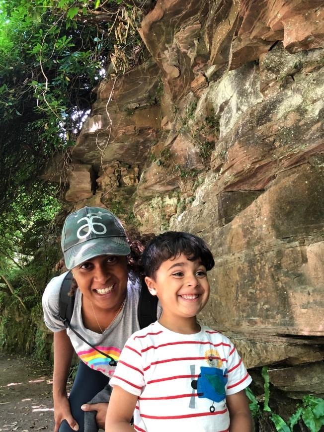Portrait of Kav and Sam under a rocky overhang.